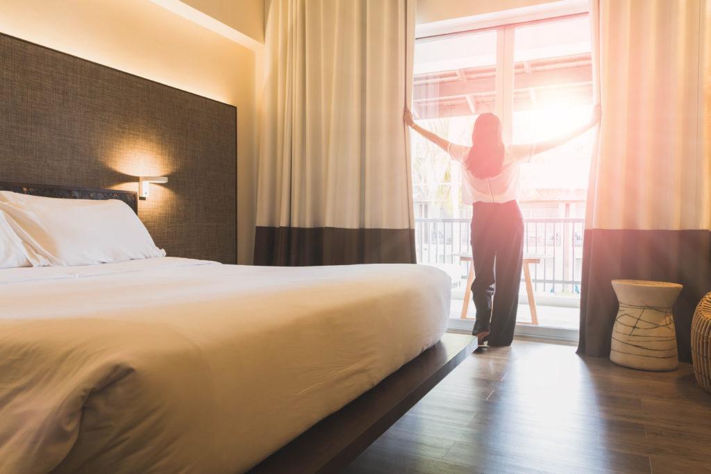 Kategoribild för sängar, kvinna vaknar upp i hotellsäng