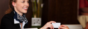 Hotel receptionist handing over gift card